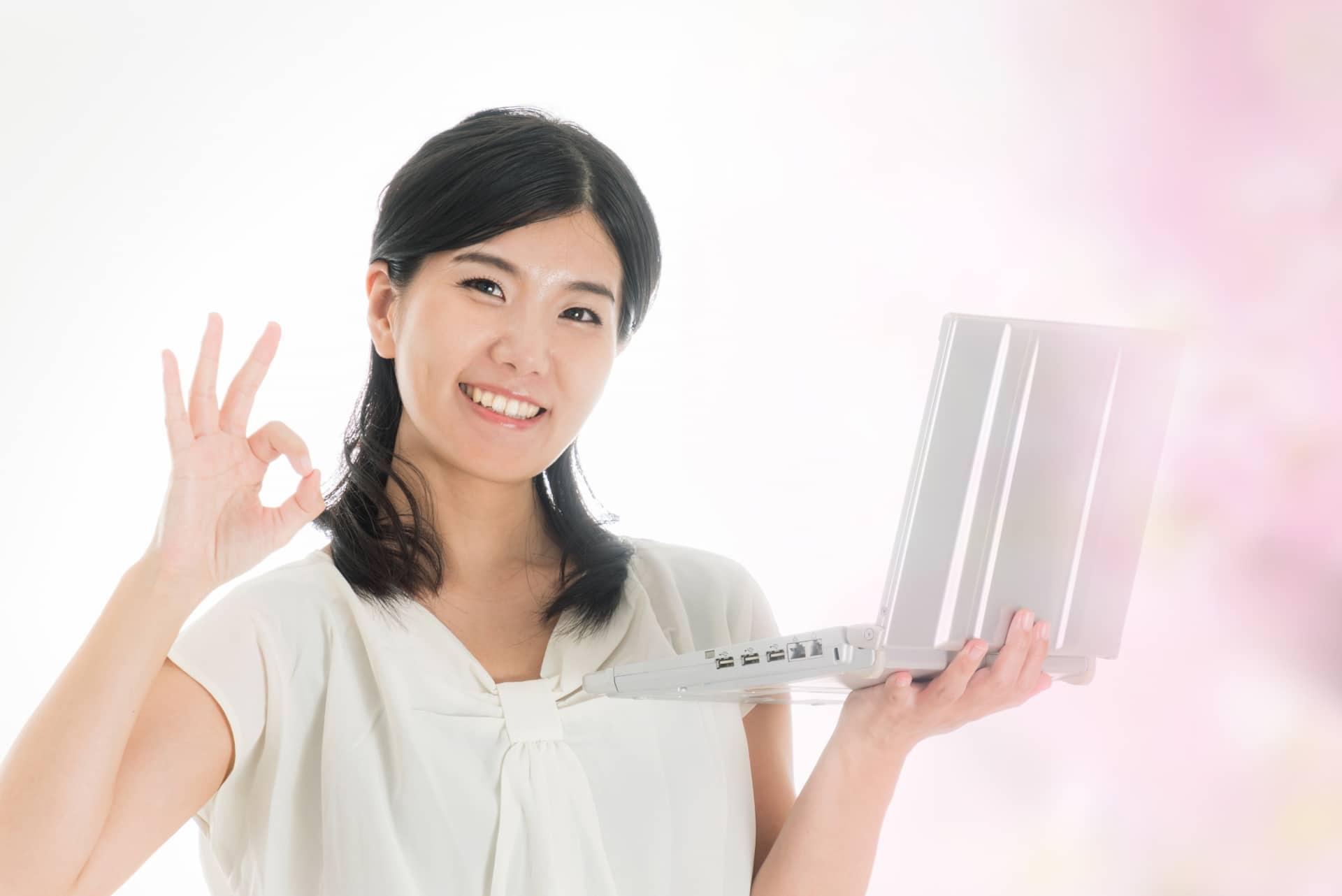 PCを手に喜びの表情を浮かべる女性