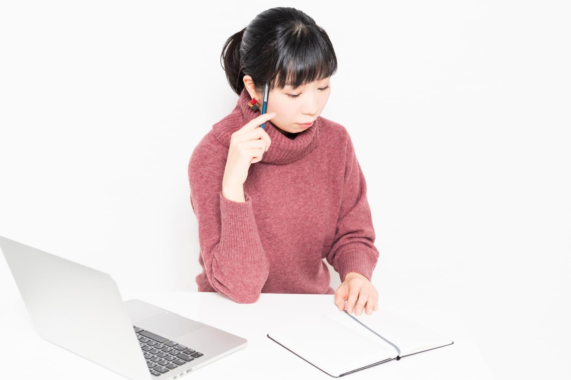 ノートを開き考える女性
