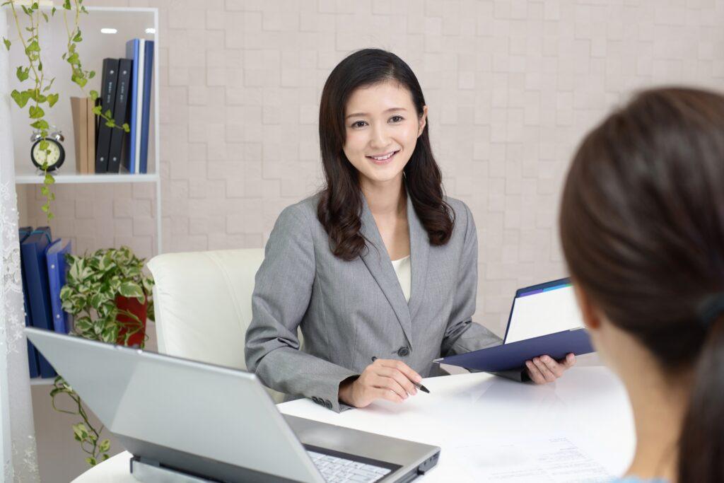 相談を受けるスーツの女性、ノートパソコン