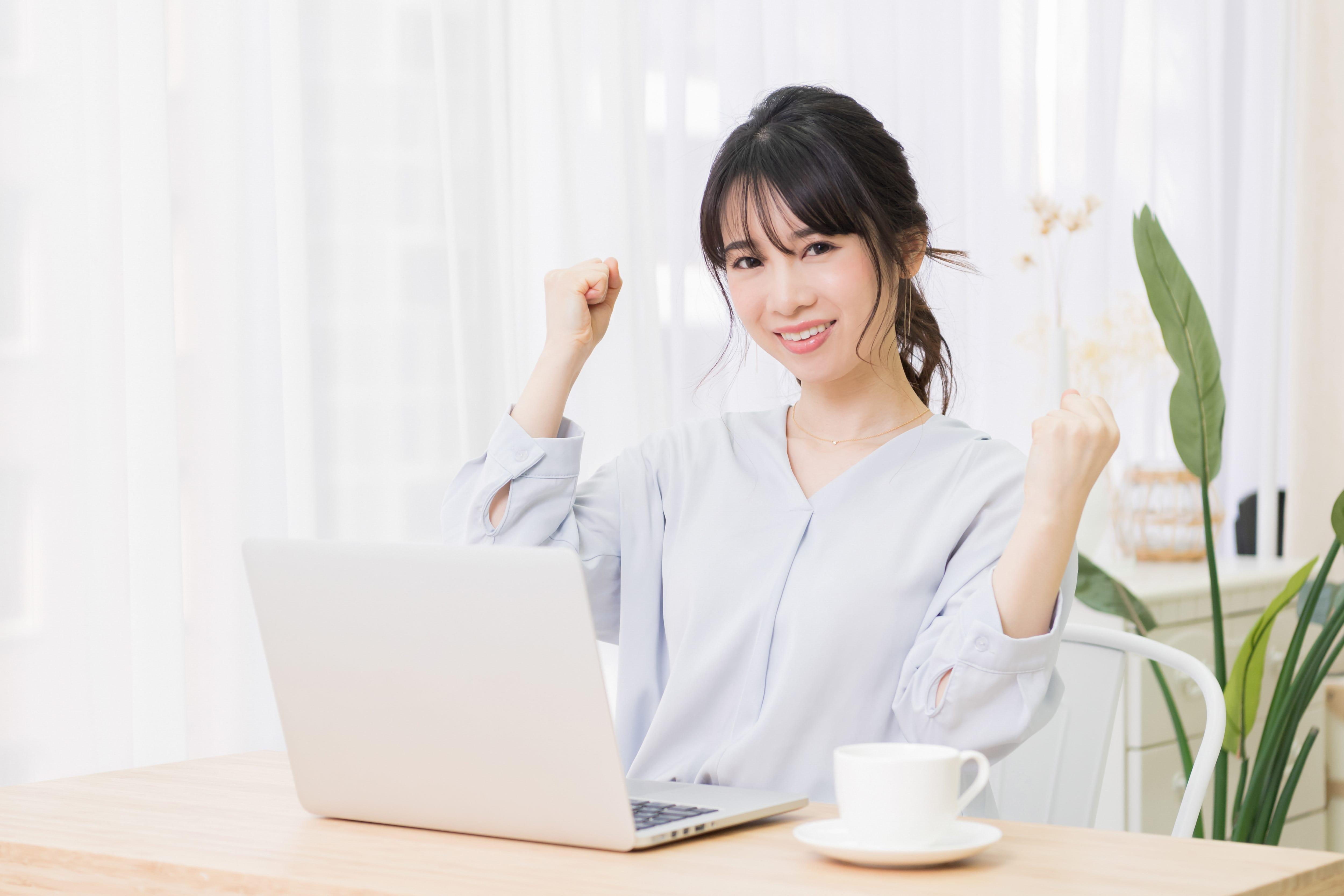 ノートパソコンの前でガッツポーズする女性