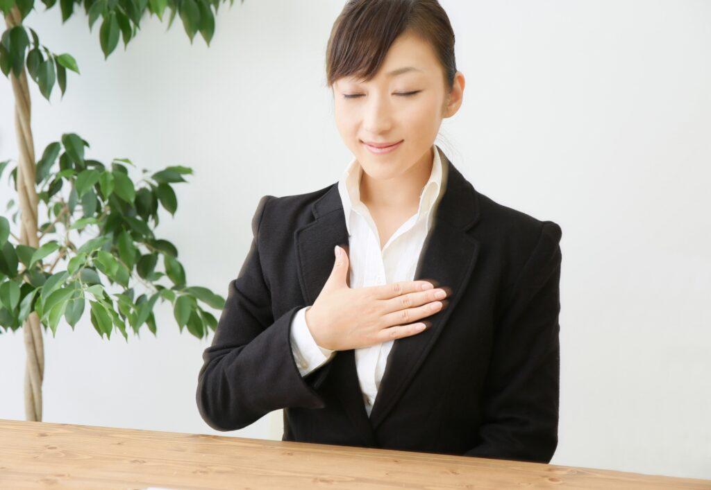 スーツの女性、胸に手を当てる