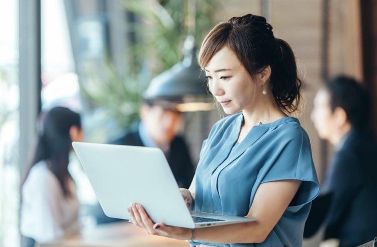 パソコンを手に作業している女性