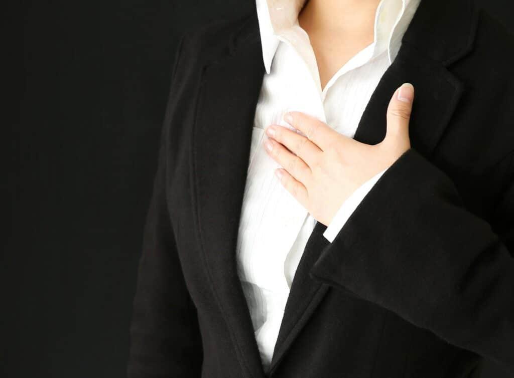 胸に手をあてて緊張する女性