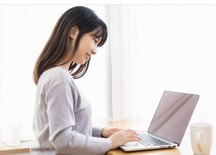 パソコンで調べている女性