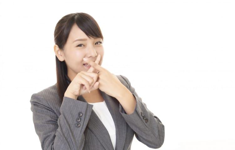 口の前でバツを作る女性