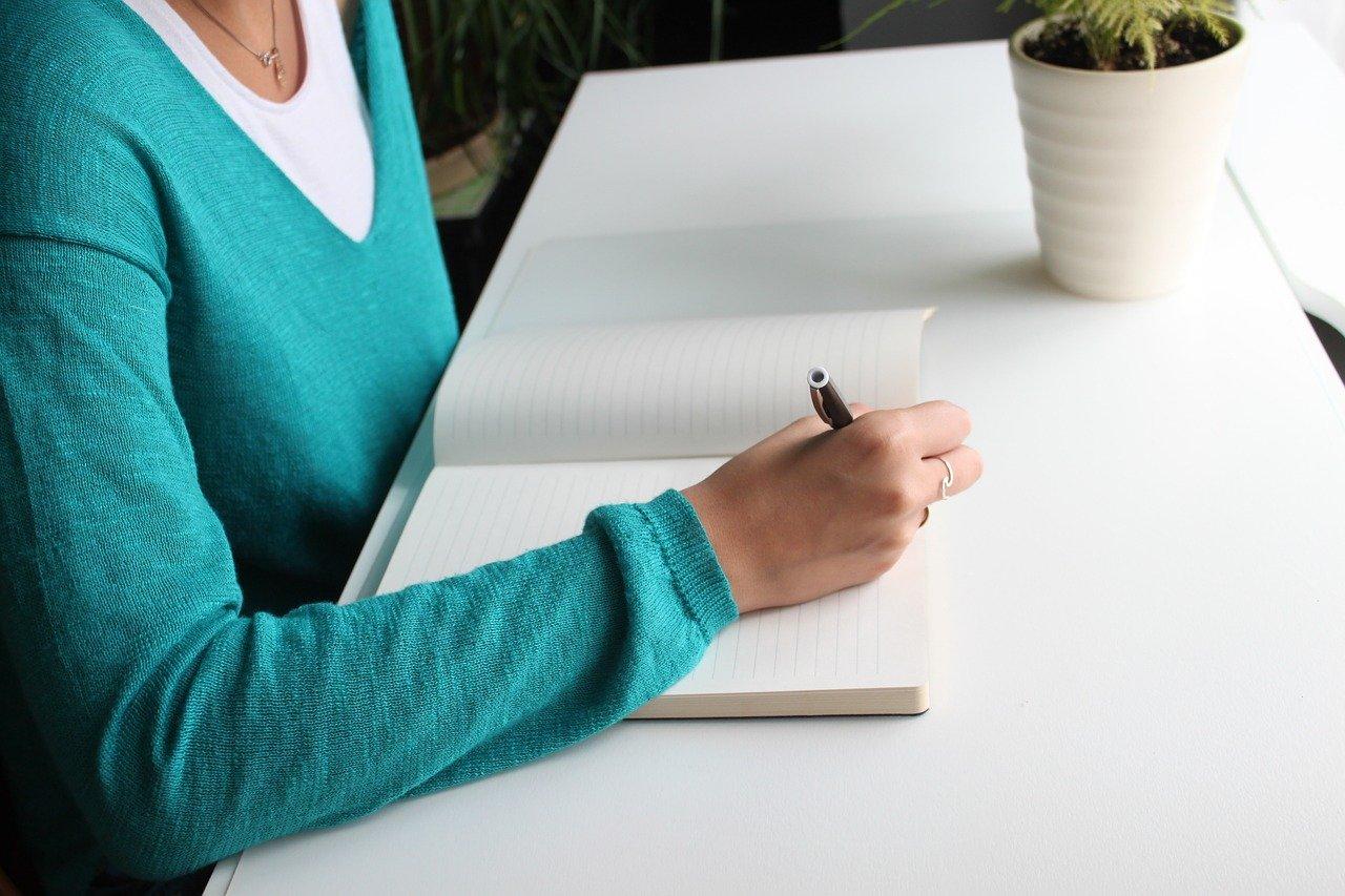 ノートに書く女性の画像