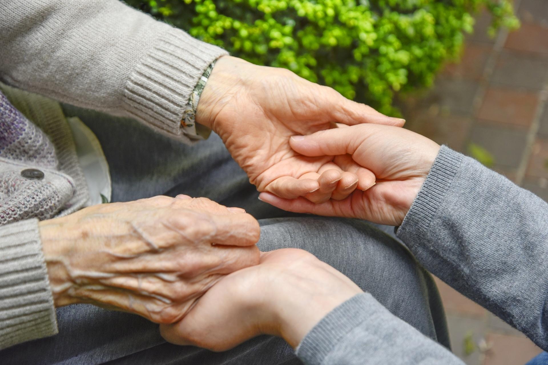 手をつなぐ高齢者と介護士