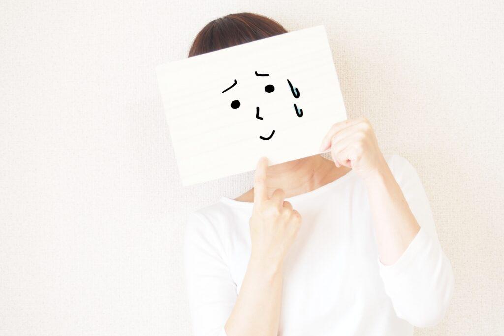 困り顔の絵を持つ女性