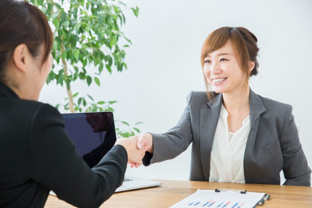 笑顔で握手する営業の女性