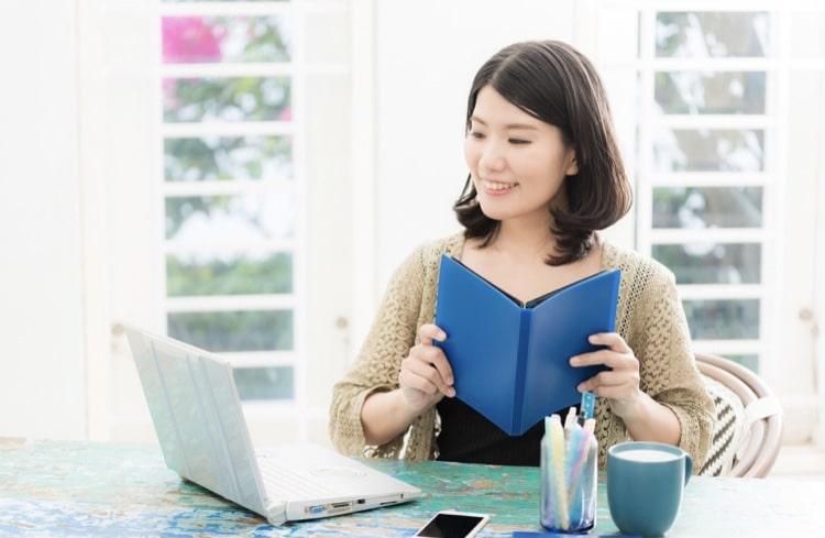 パソコンと本を見る女性