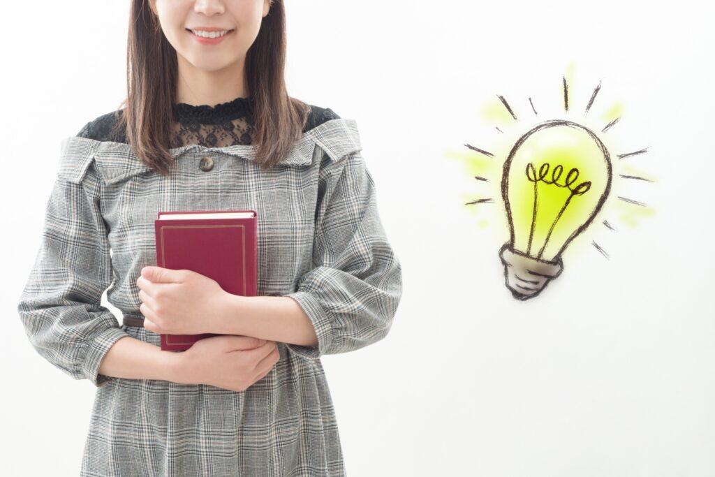 本を抱える女性、電球のマーク
