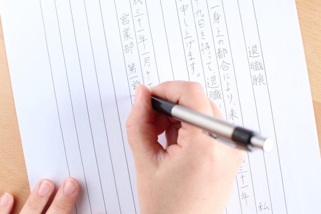 退職届を書く女性の手