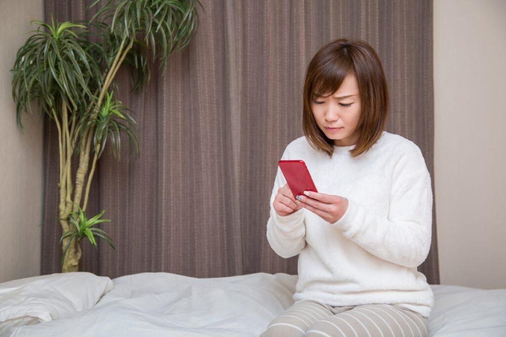 ベッドに座りスマホを操作する女性