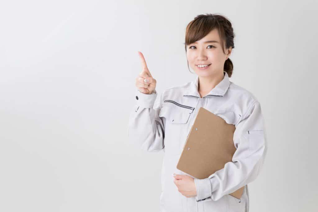 人差し指をたてる作業着の女性
