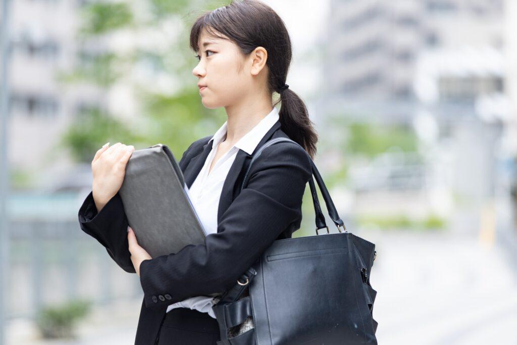鞄に入らず書類を手に持つ女性