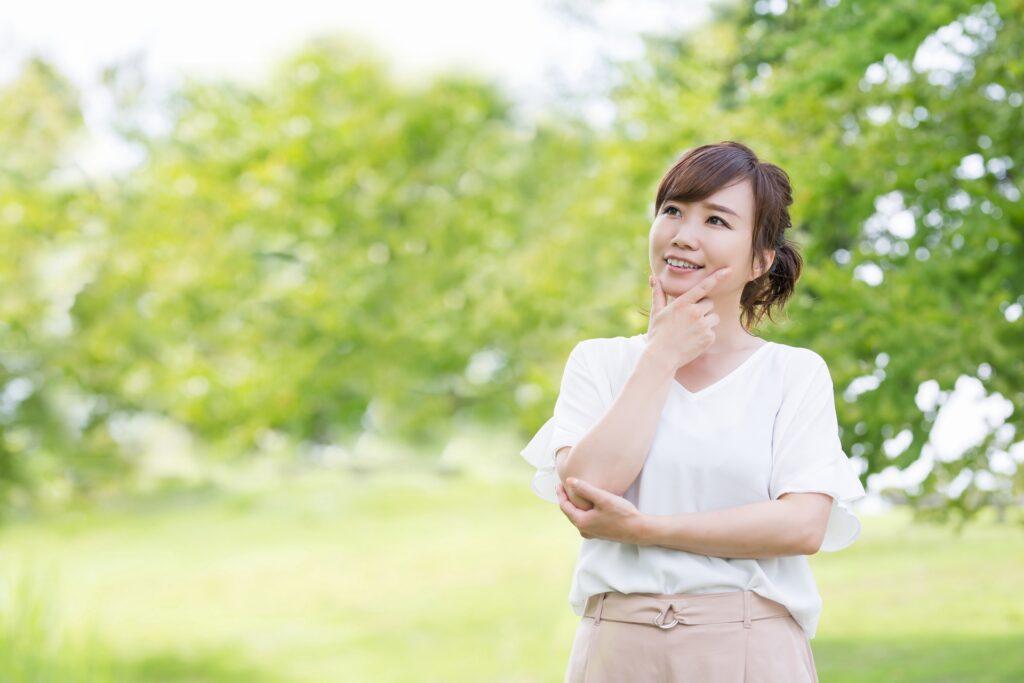 新緑の中で考える女性