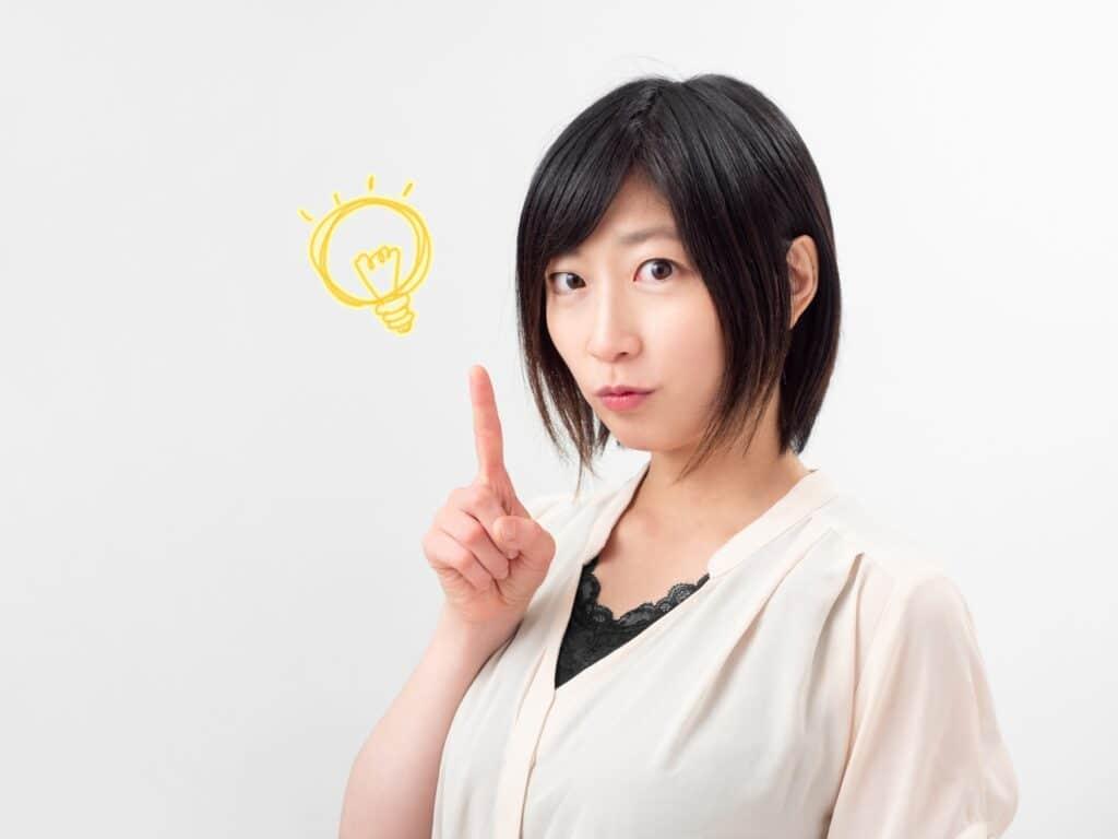 人差し指を立てる女性、電球