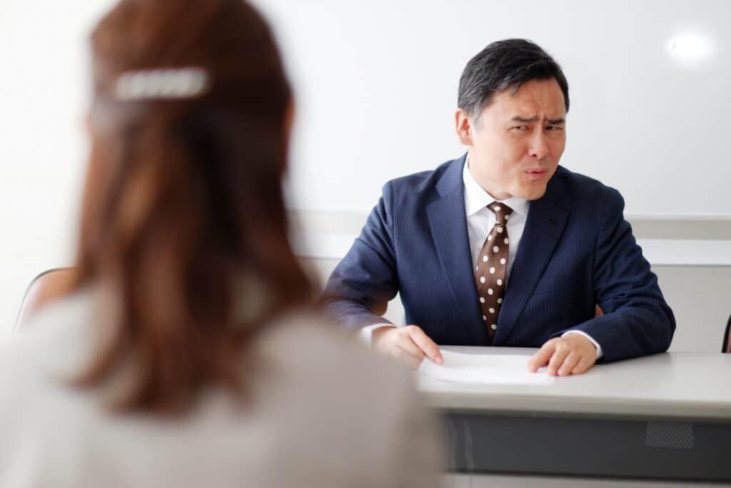 いぶかしむ男性の社員と面談する女性