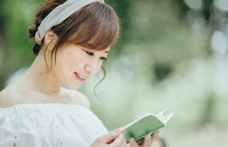 本を見て笑顔の女性
