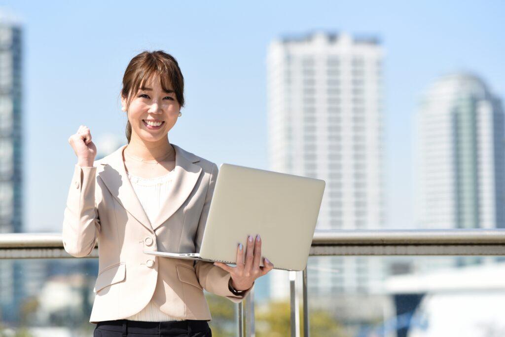 ノートパソコンを持つ女性、オフィスビル