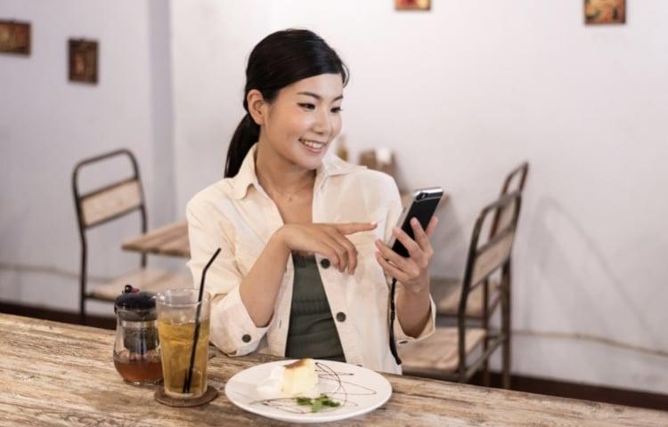 携帯ゲームをしている女性
