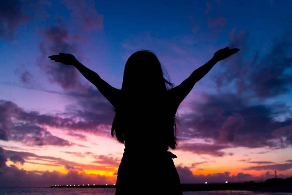 両手を広げる女性のシルエット、夕焼け