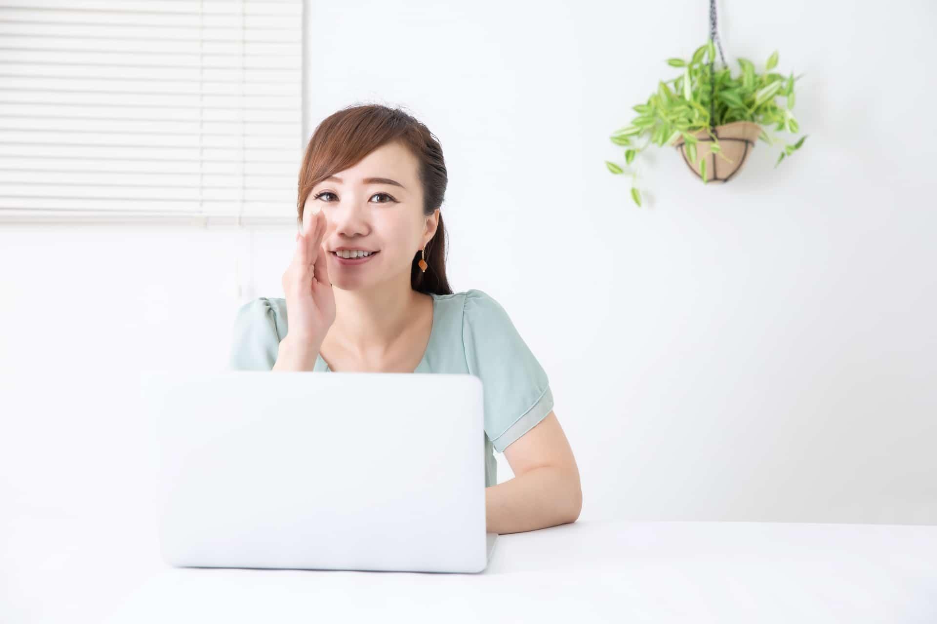 ノートパソコン、口に手を当てる女性