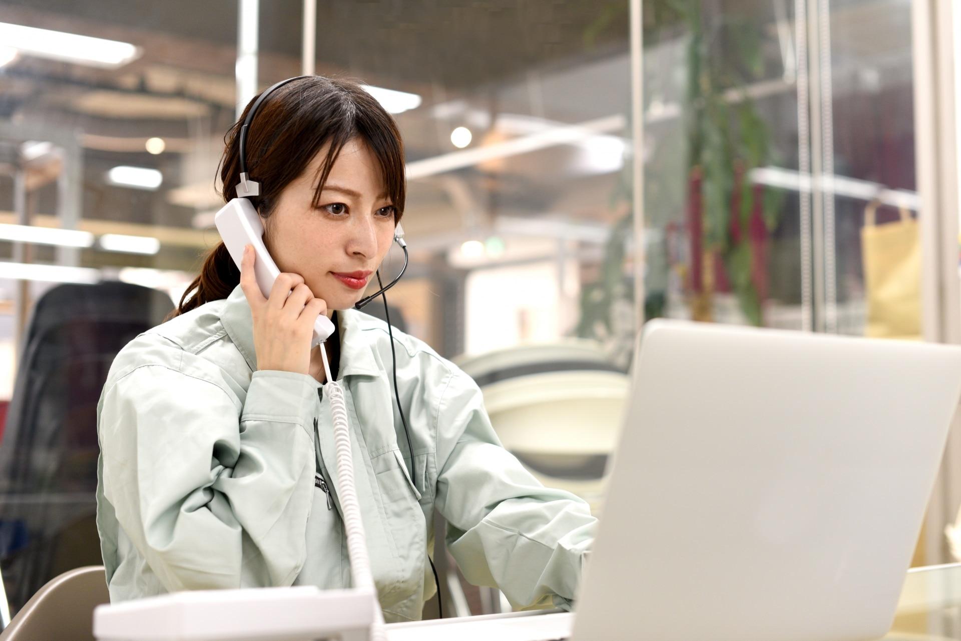 パソコン、電話する女性