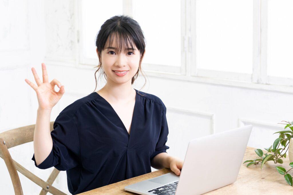 手で丸を作る女性、ノートパソコン