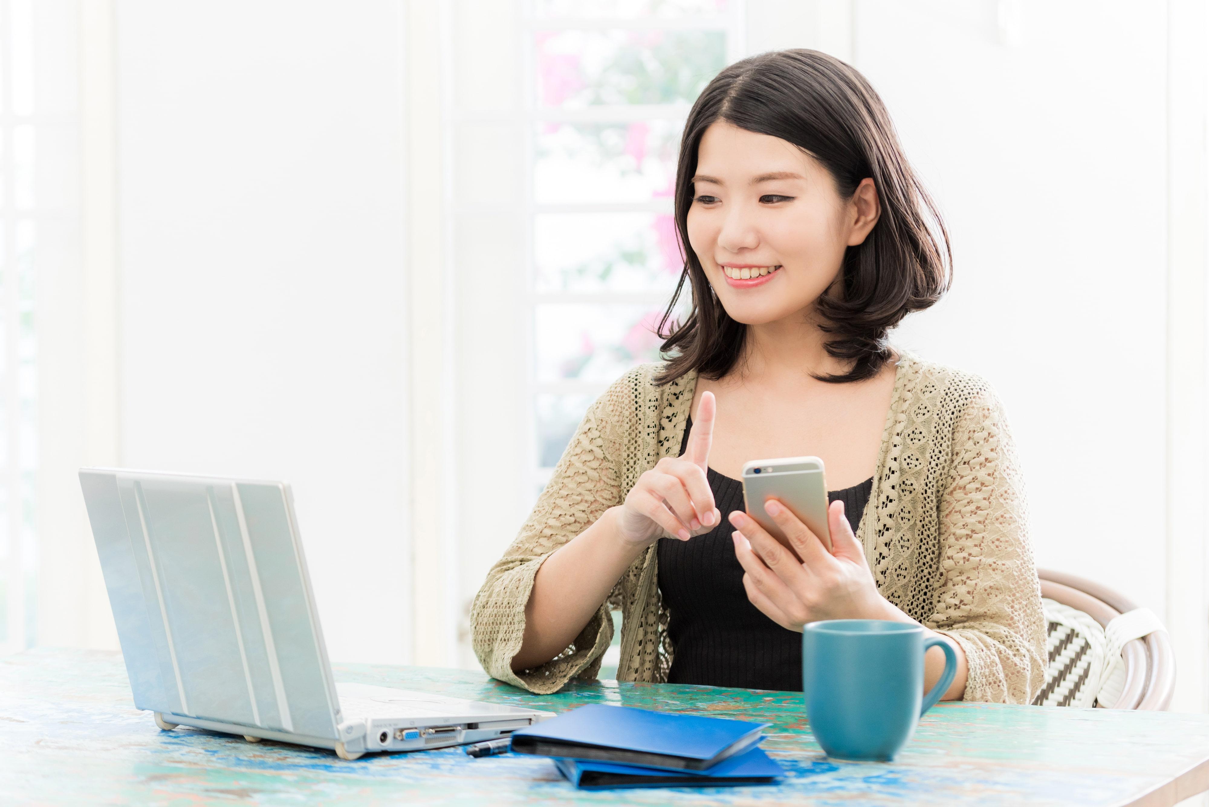 パソコンとスマホを操作する女性の画像