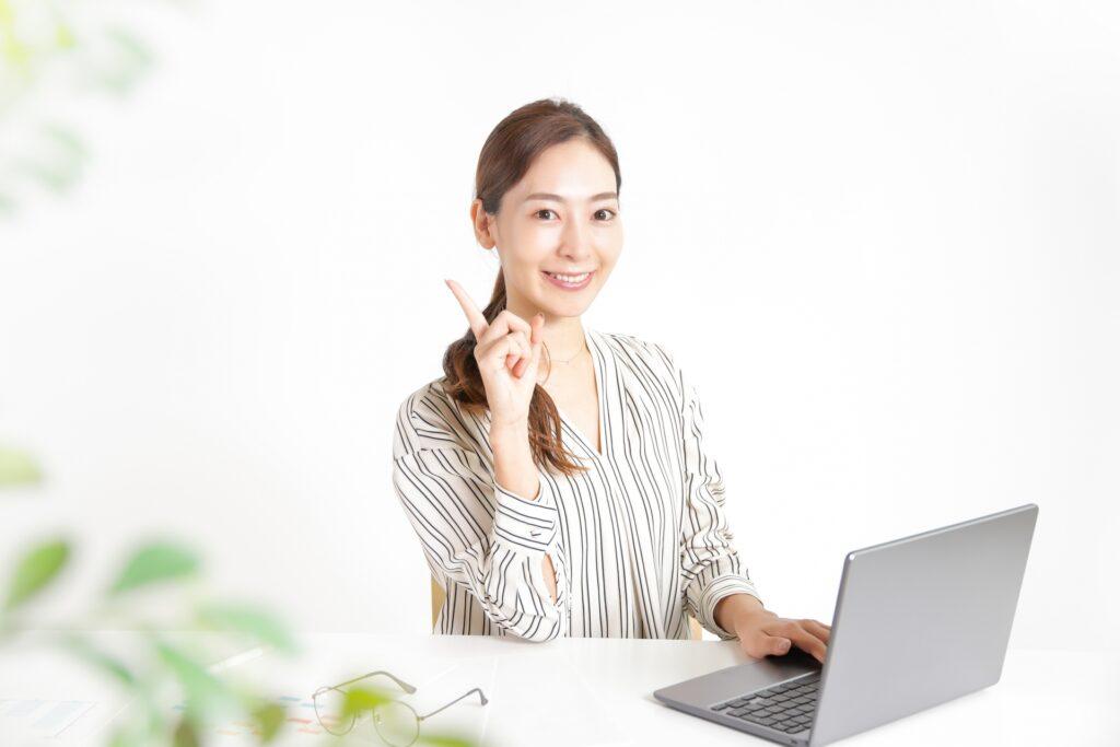 ノートパソコン、人差し指を立てる女性