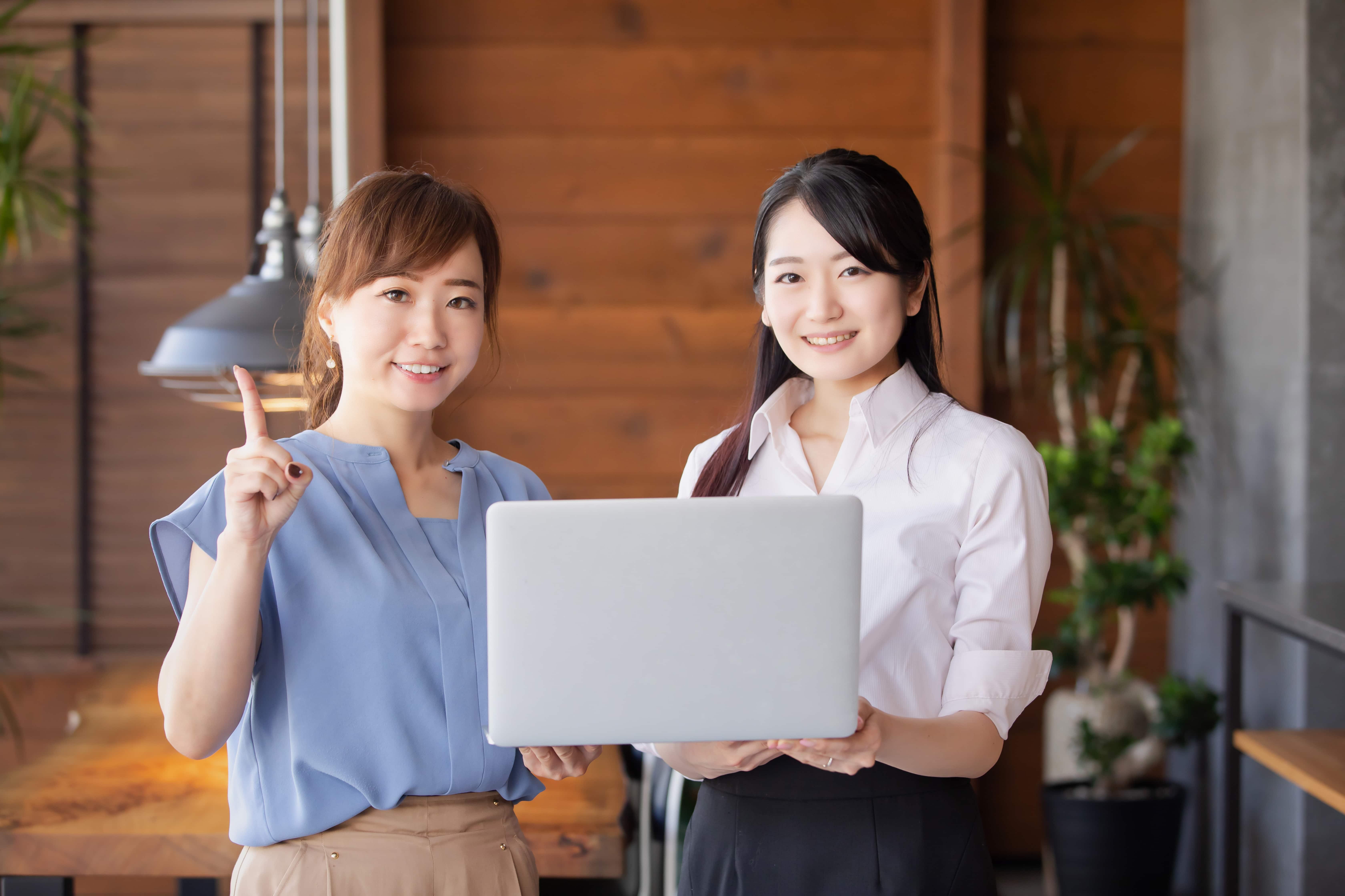 パソコンを持つ女性スタッフ