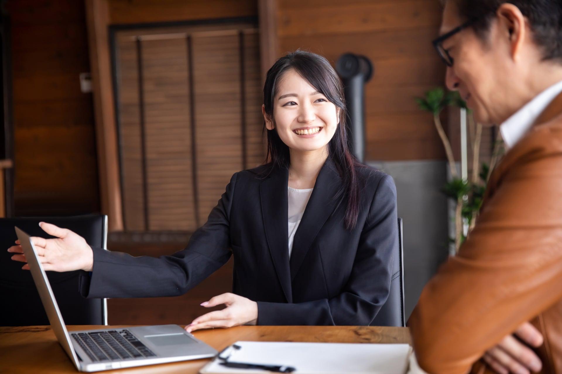 プレゼンをする女性、ノートパソコン、顧客の男性