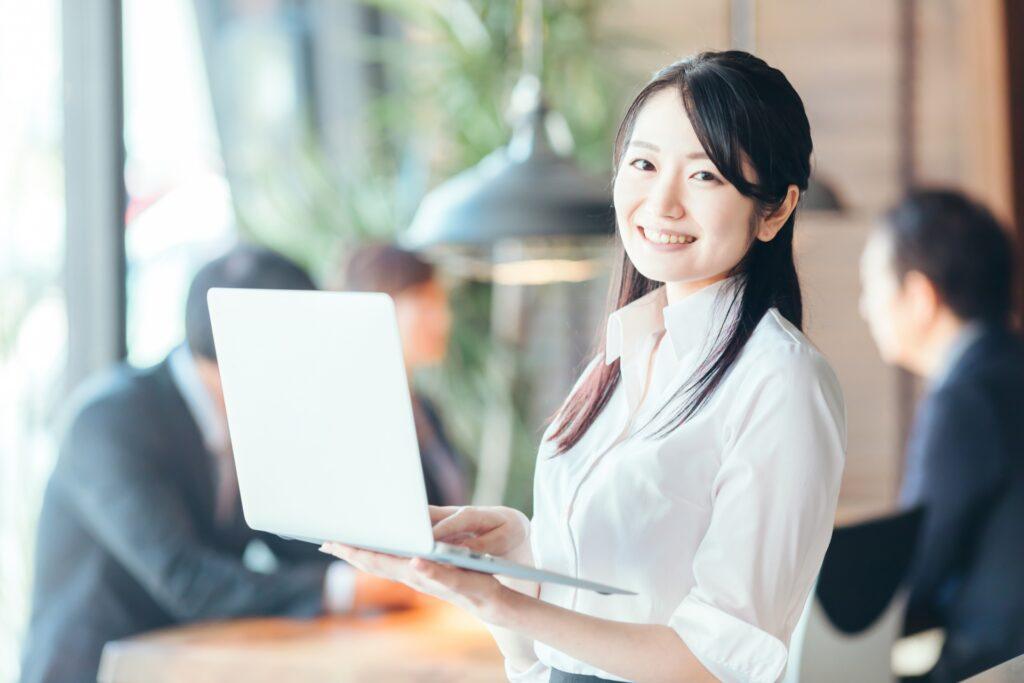 ノートパソコンをもつ笑顔の女性