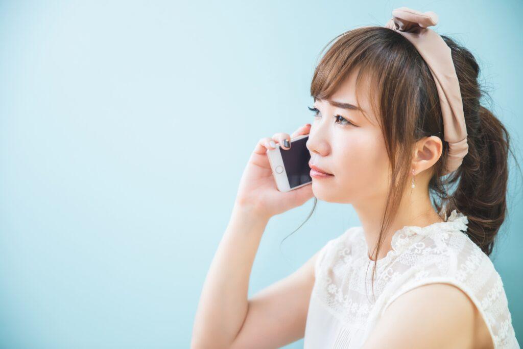スマホで電話しながら困る女性