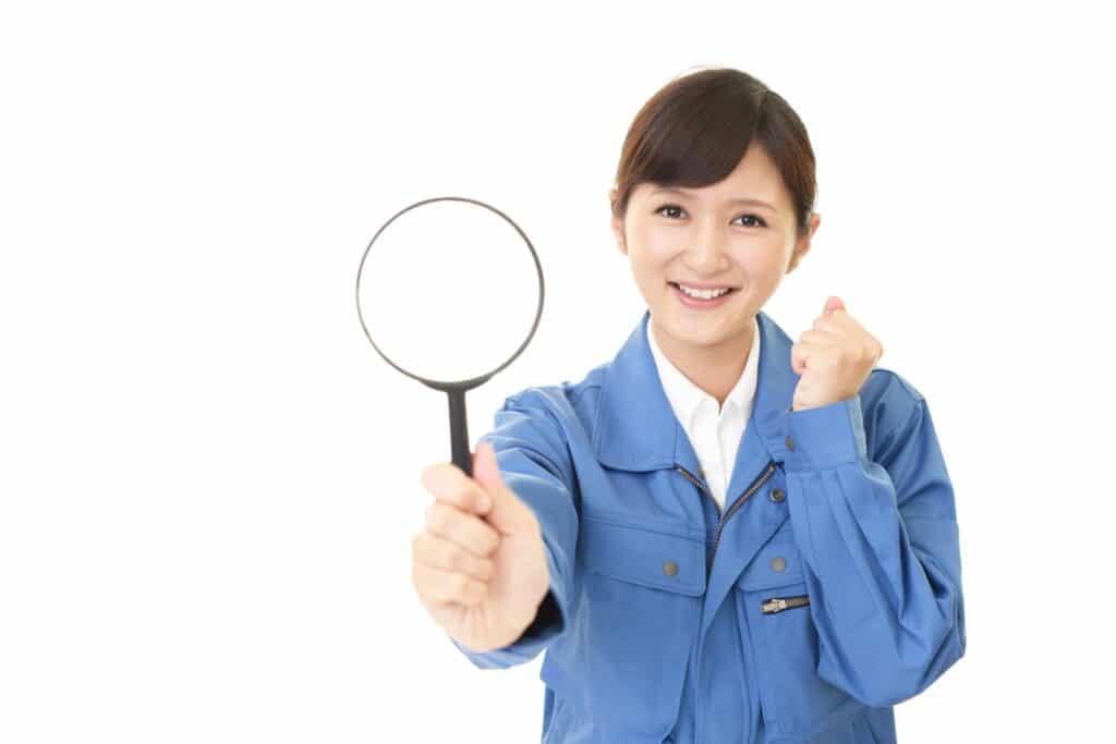 虫眼鏡、作業着の女性