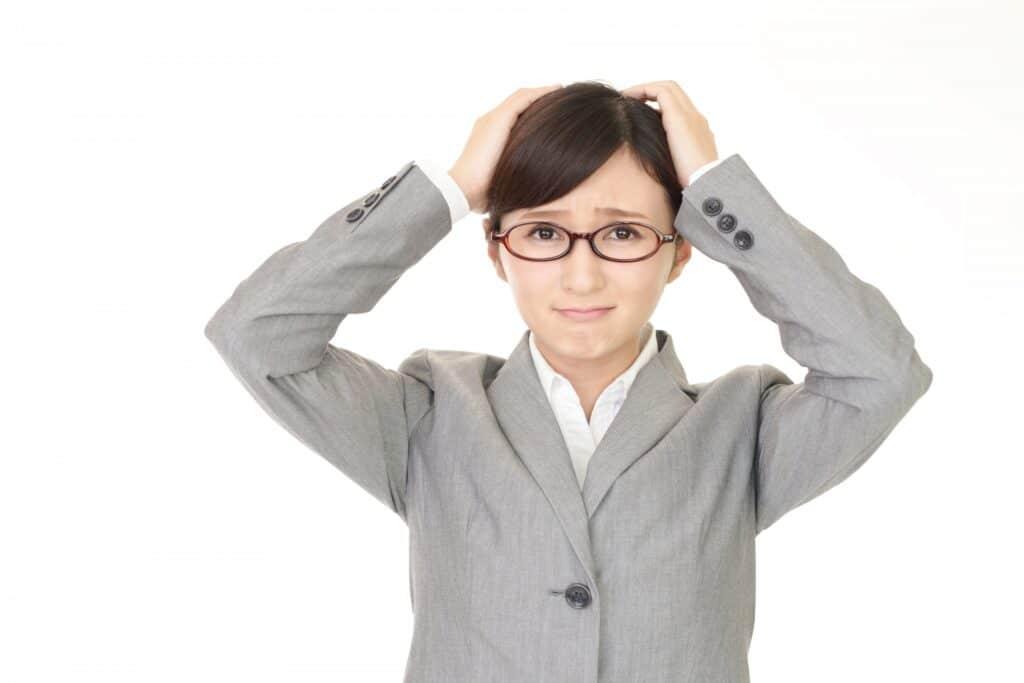 困り顔で頭を抱えるメガネの女性