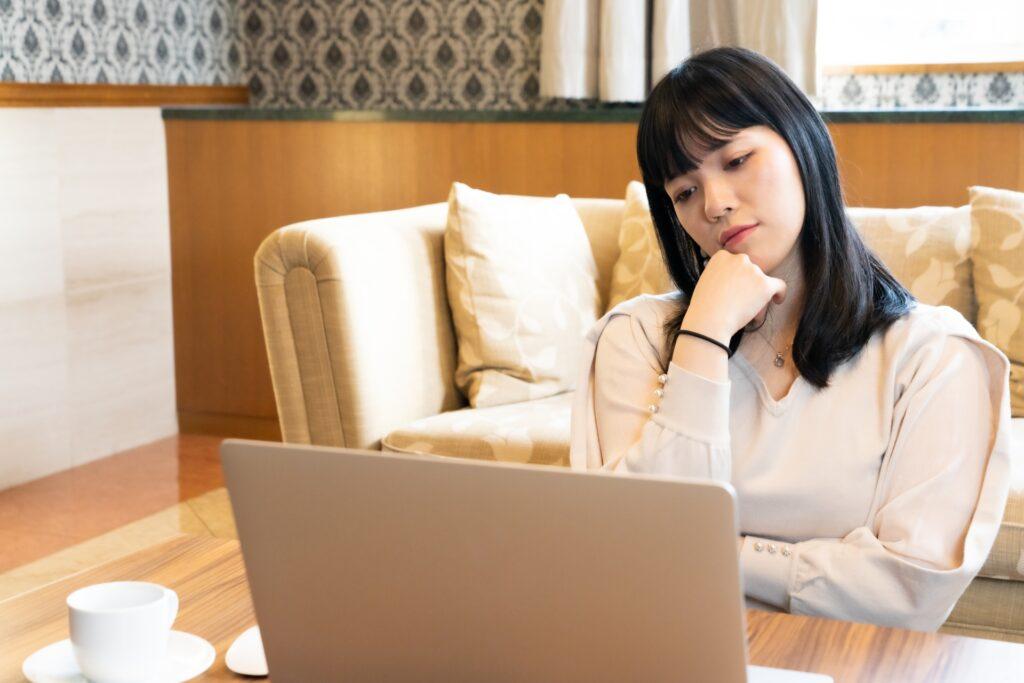 ノートパソコンを見て悩む女性