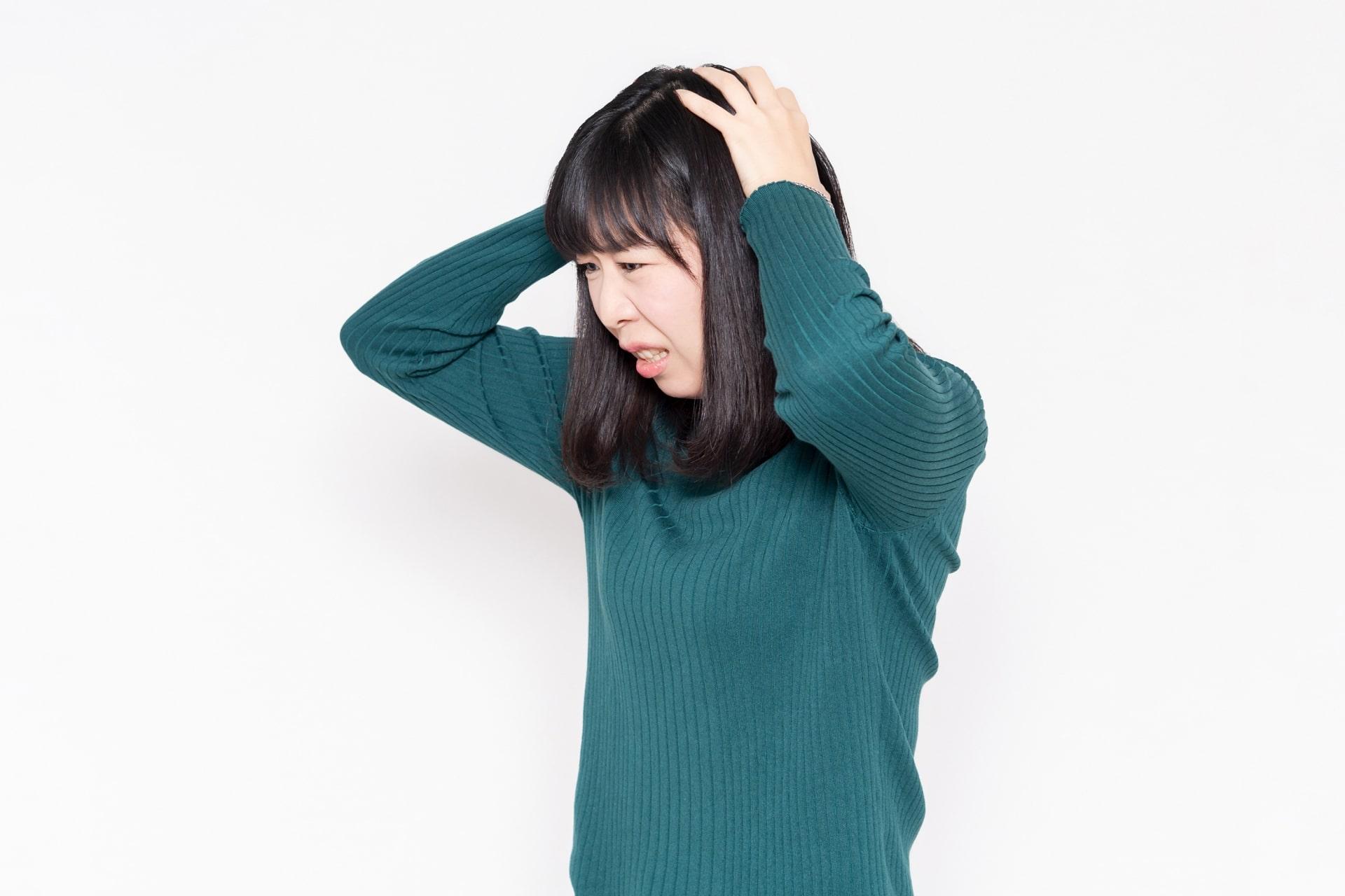 頭をかかえる女性の画像