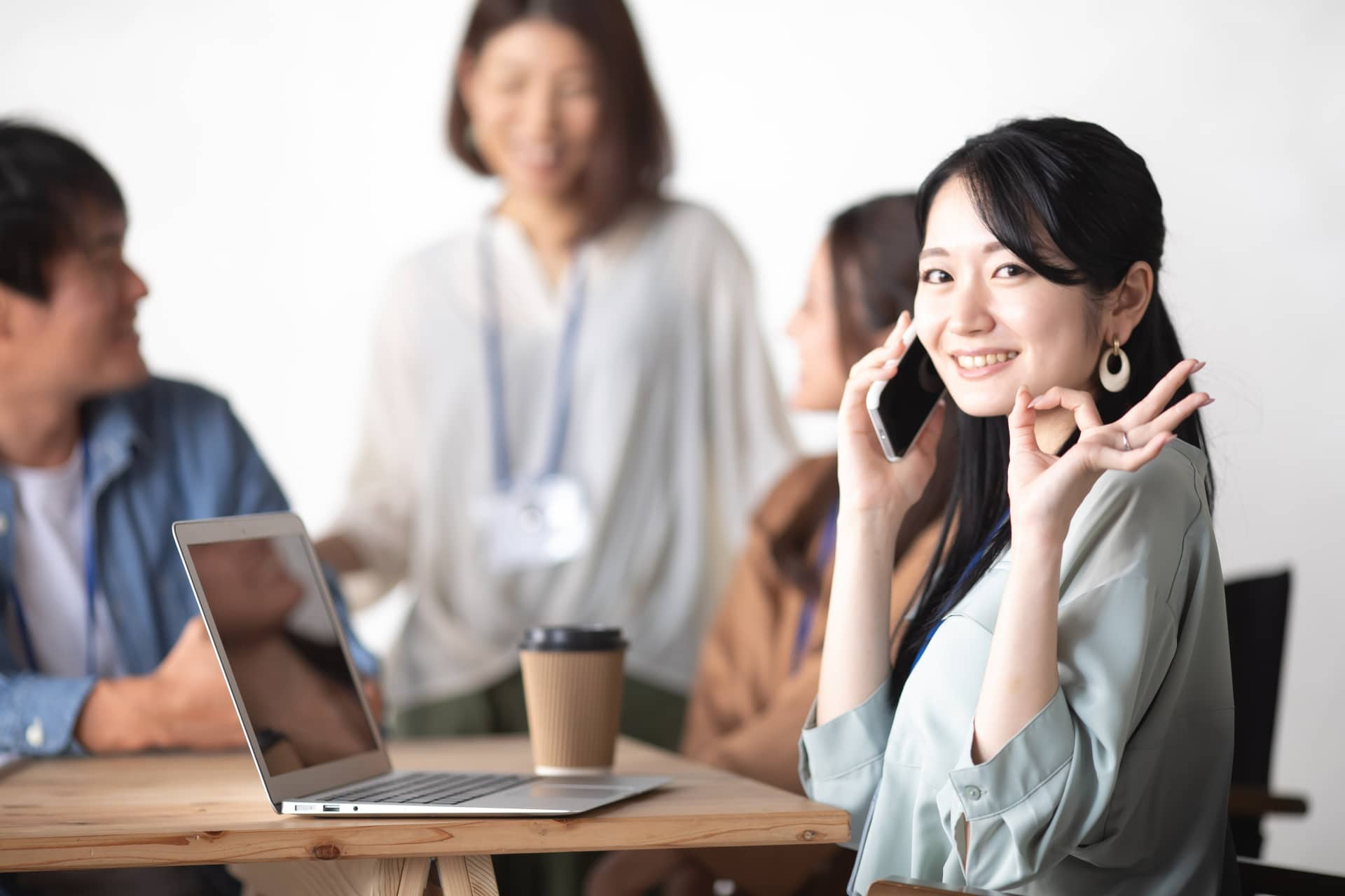 ミーティング中の女性、スマホ、ノートPC