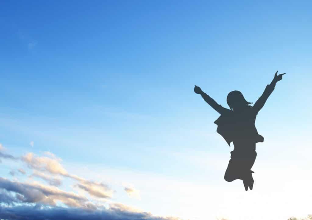 ジャンプする女性のシルエット、青空