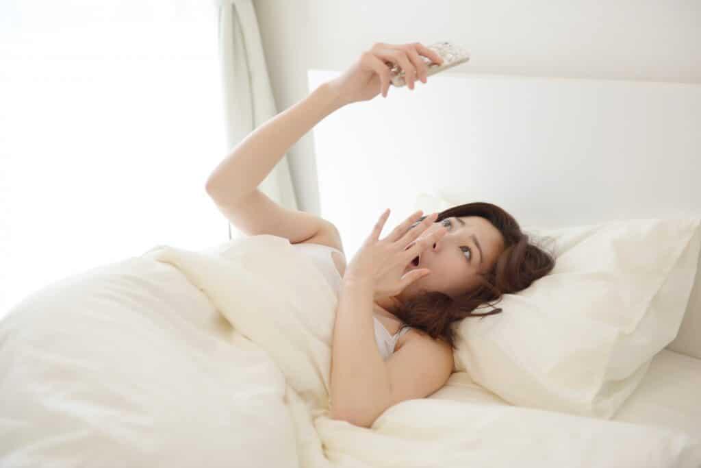 ベッドでスマホをみて驚く女性