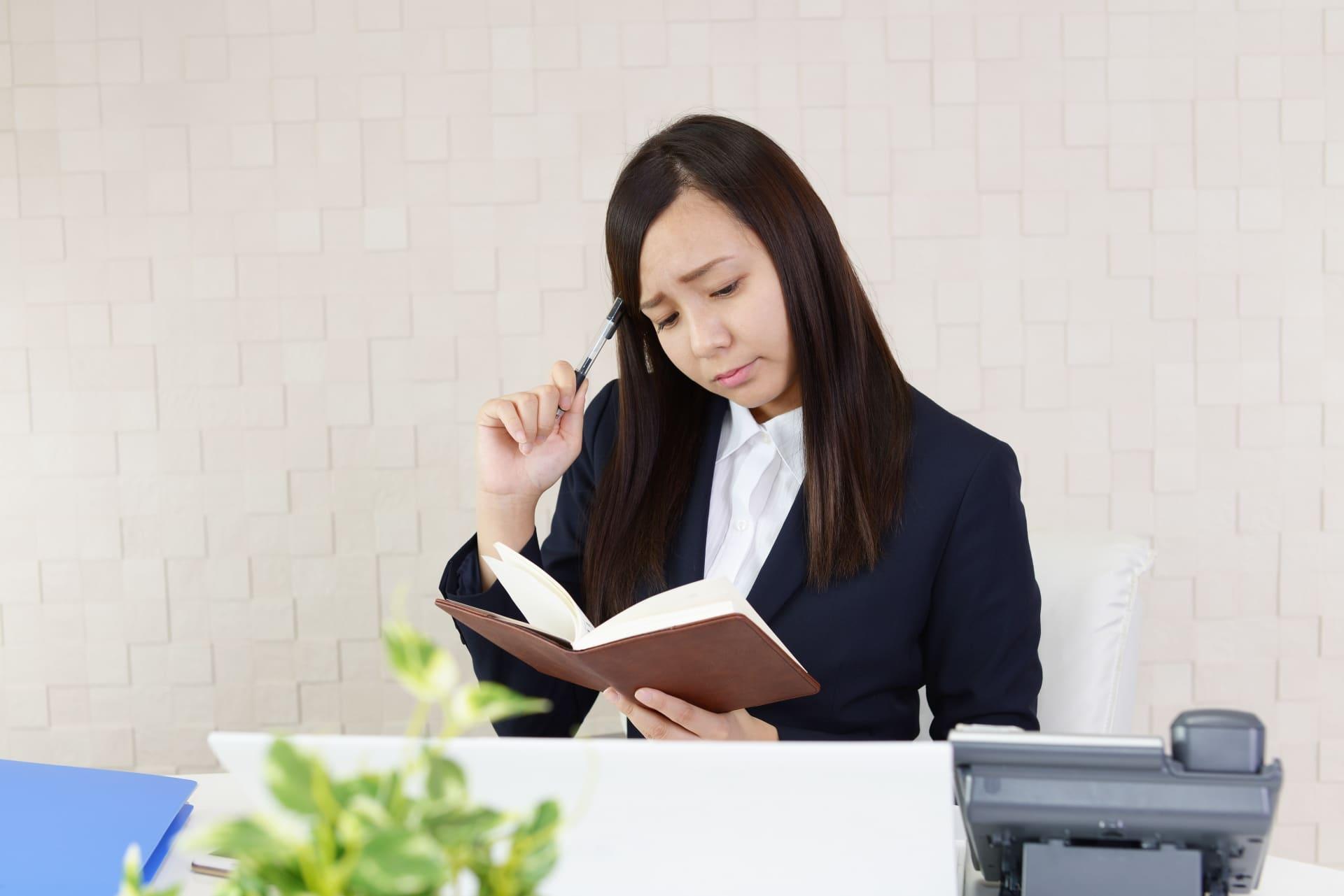 手帳を見て悩む女性、オフィス