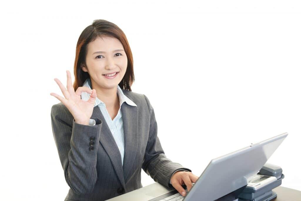 ノートパソコン、手で丸をつくる女性