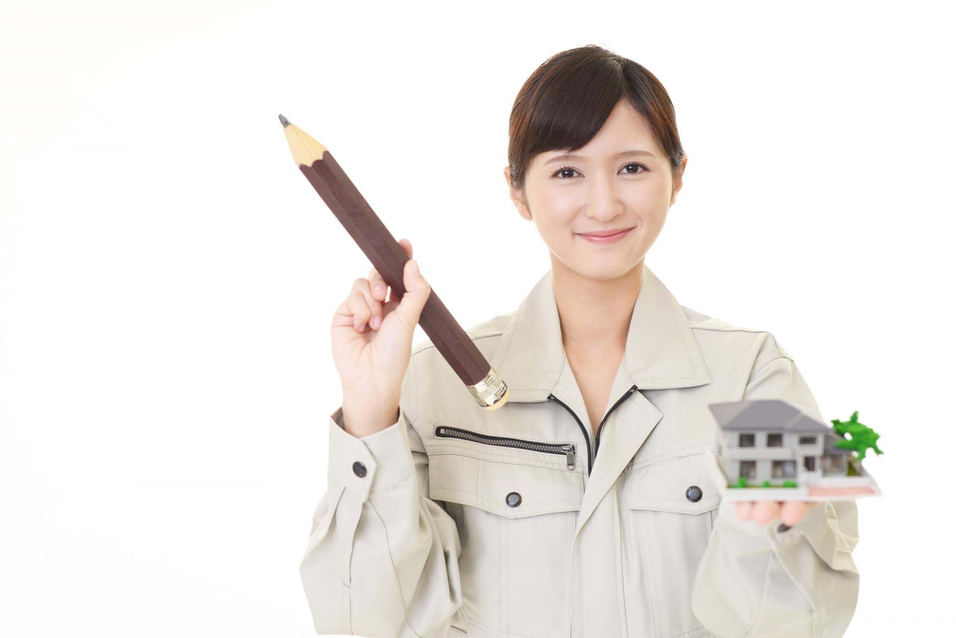 住宅の模型と鉛筆をもつ女性