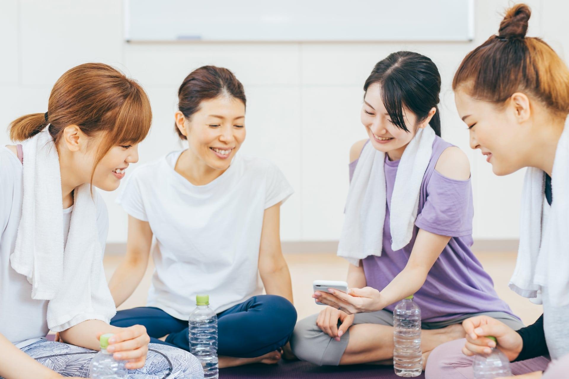 スマホを見て談笑する女性たち