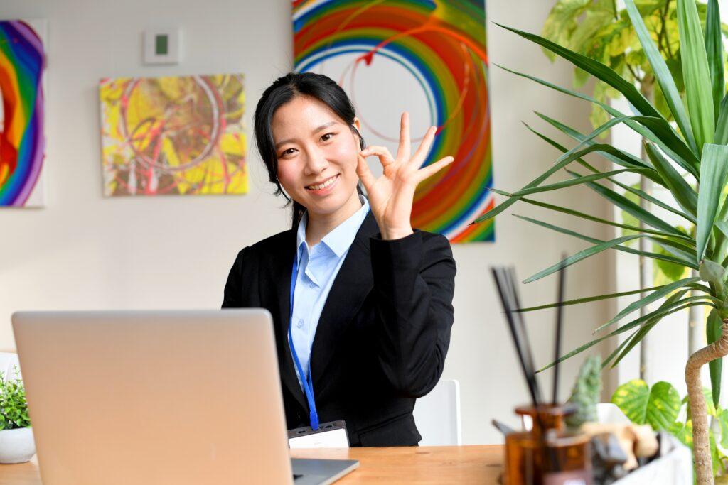 パソコンとOKサインをする女性