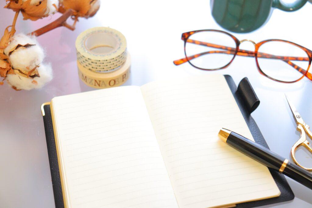 スケジュール帳、ペン、メガネ