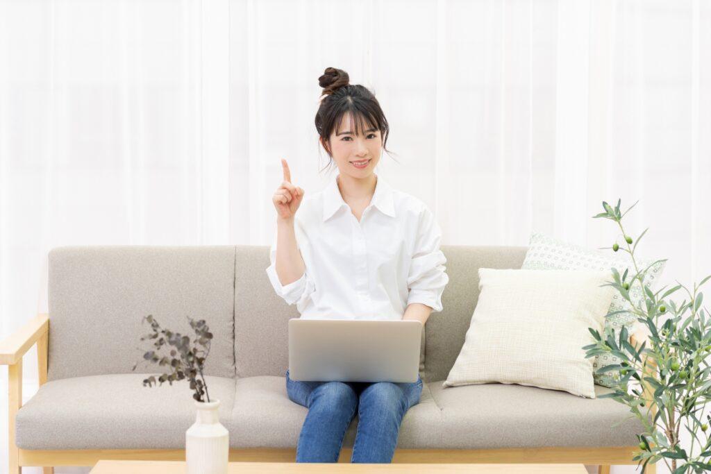 ソファ、人差し指を立てる女性