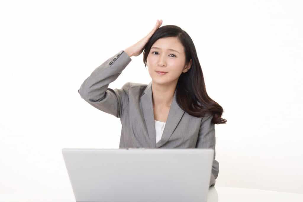 頭を抱える女性、ノートパソコン